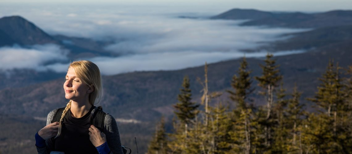 Woman Enjoying the Fresh Air of the Mountains while Hiking to the summit of the Richardson in Gaspe, Canada.